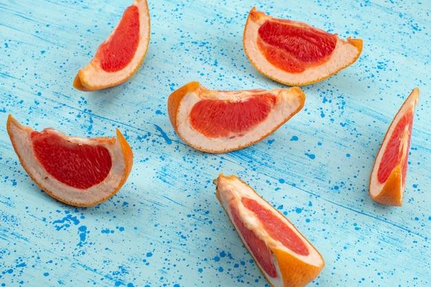 Vista superior em fatias de laranja suculenta madura sobre o fundo azul brilhante