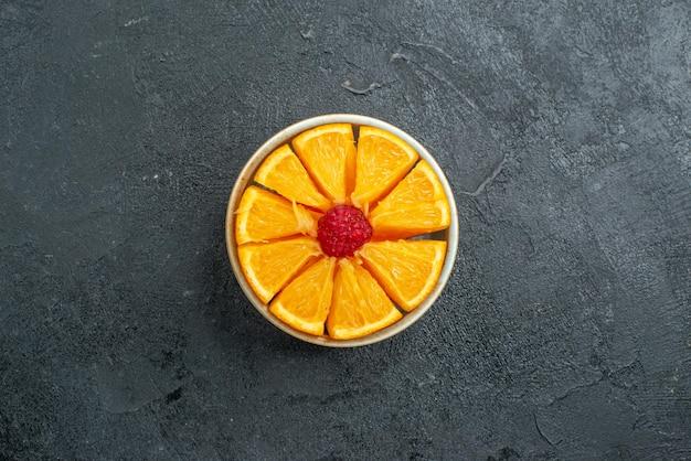 Vista superior em fatias de laranjas frescas dentro do prato em uma superfície escura com frutas cítricas exóticas