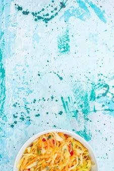 Vista superior em fatias de legumes frescos longos e salada fina em pedaços dentro de um prato redondo na mesa azul