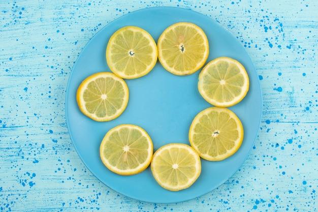Vista superior em fatias de limão maduro suculento azedo dentro placa azul no chão azul brilhante Foto gratuita