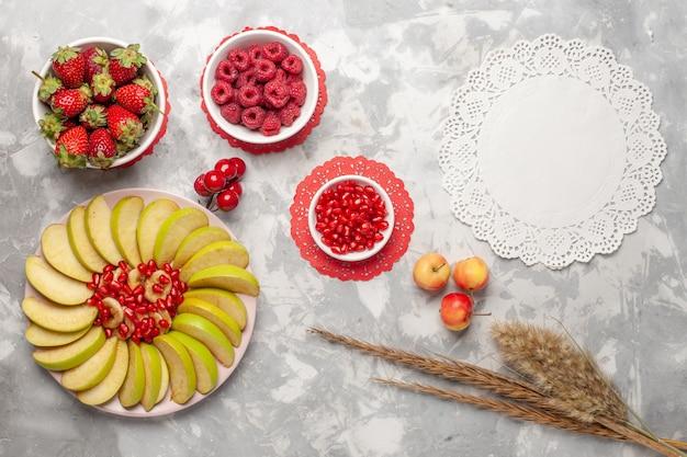 Vista superior em fatias de maçãs verdes com framboesas e morangos na superfície branca frutas baga tropical exótico fresco