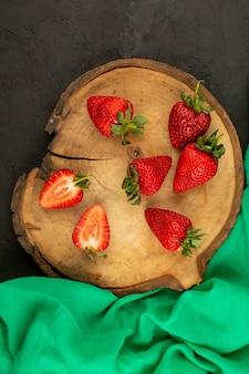 Vista superior em fatias de morangos vermelhos maduros na mesa de madeira marrom e piso escuro