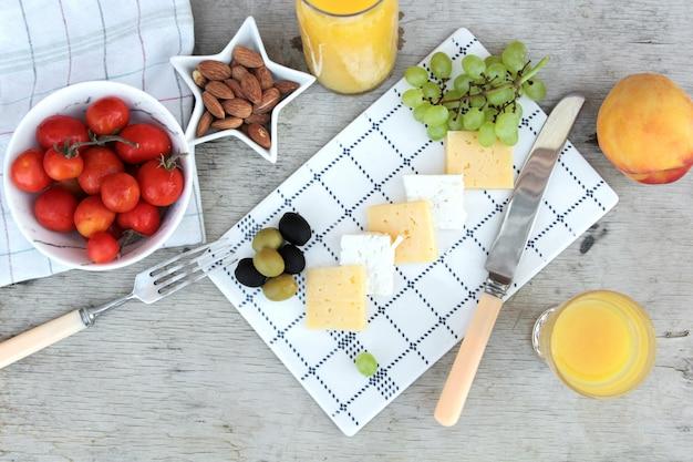 Vista superior em fatias de queijo com azeitonas uvas tomates e suco de laranja
