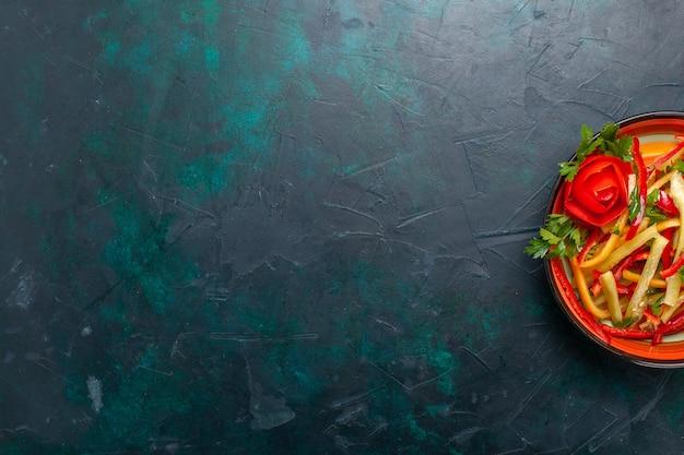 Vista superior em fatias de salada de diferentes cores de pimentão dentro do prato no fundo escuro