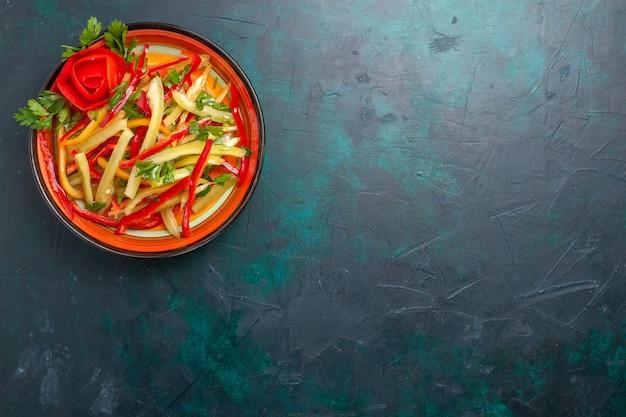 Vista superior em fatias de salada de vegetais de cores diferentes de pimentão dentro do prato no fundo azul escuro