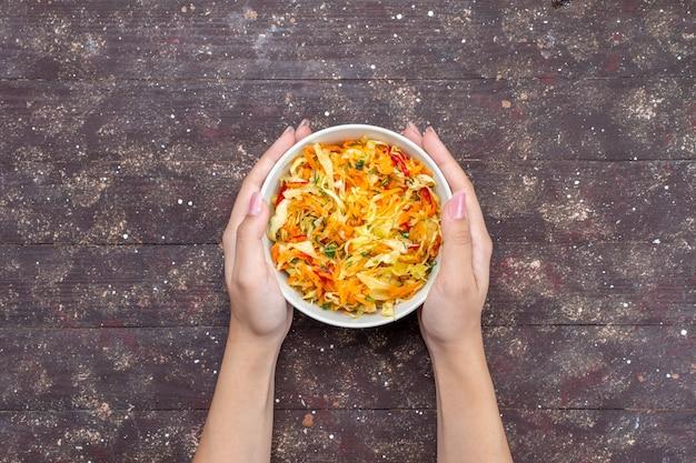 Vista superior em fatias de salada de vegetais frescos e salgados dentro do prato no fundo marrom rústico com comida vegetal foto fresca