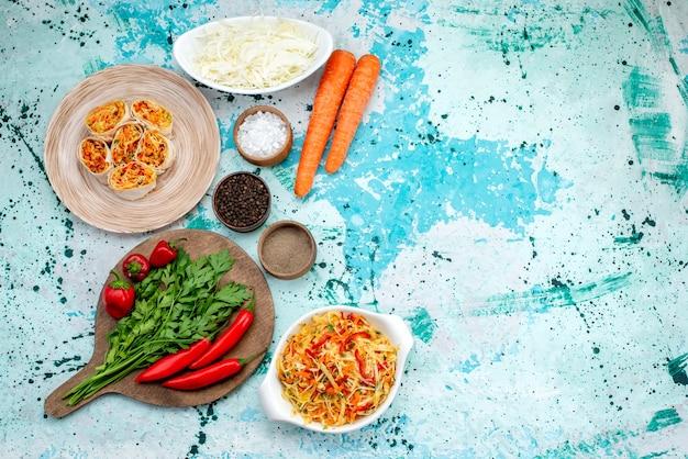 Vista superior em fatias de vegetais em fatias de massa com recheio saboroso, juntamente com cenouras verdes e pimentões vermelhos picantes na mesa azul brilhante, lanche de refeição de rolo de cor de comida