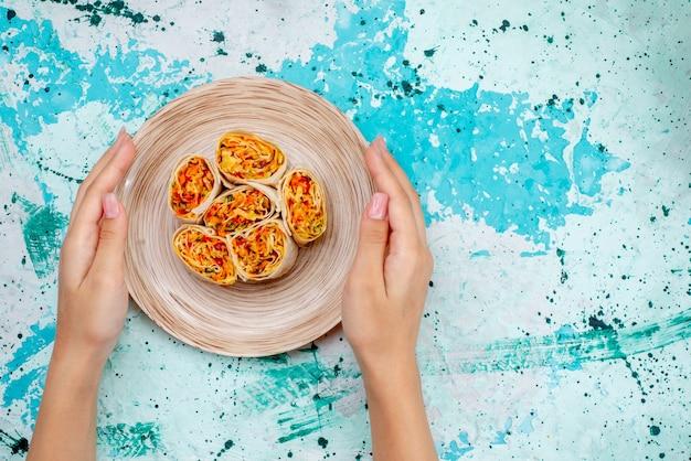 Vista superior em fatias de vegetais em fatias de massa com recheio saboroso, segurando por uma fêmea na mesa azul brilhante com comida em rolo