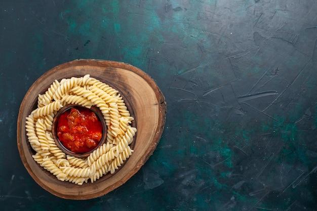 Vista superior em forma de massa italiana com molho de tomate em fundo azul escuro