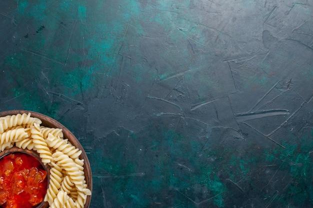 Vista superior em forma de massa italiana com molho de tomate na mesa azul escura