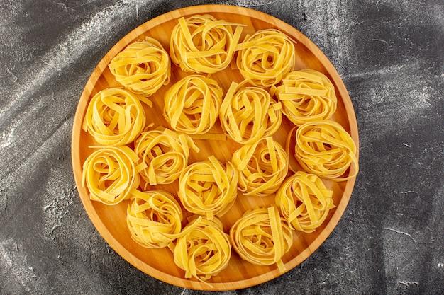 Vista superior em forma de massa italiana em forma de flor crua e amarela na mesa de madeira espaguete de refeição de comida crua italiana