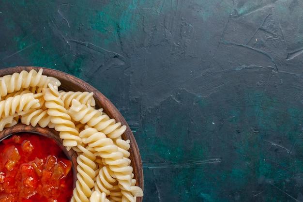 Vista superior em formato de massa italiana com molho de tomate em superfície azul escura