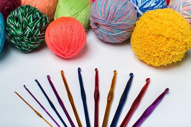 Vista superior em fundo branco com muitas bolas de lã e agulhas de tricô.