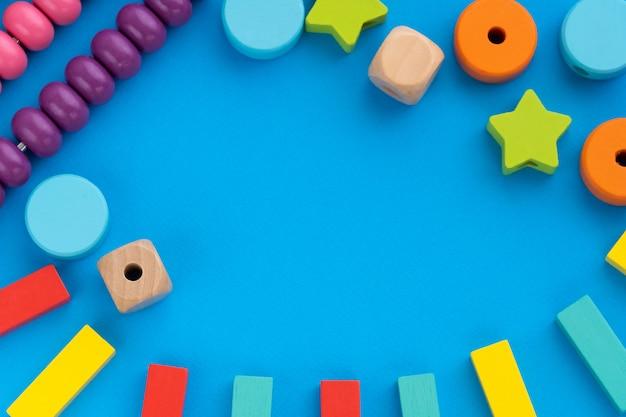 Vista superior em jogos educativos infantis, quadro com brinquedos de crianças multicoloridas em papel azul