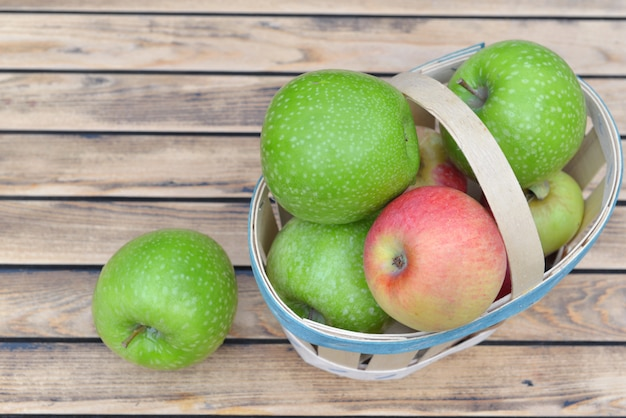 Vista superior em maçãs verdes e vermelhas em uma pequena cesta