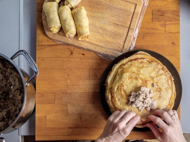 Vista superior em mãos humanas envolvendo carne, recheio de panqueca recém-assada em um fundo de madeira. panquecas enroladas com recheio são colocadas ao lado da mesa da cozinha. feriado de maslenitsa.