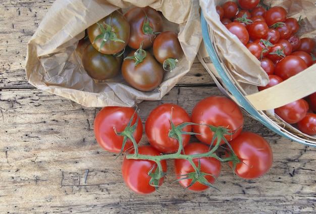 Vista superior em tomates frescos em uma pequena cesta em um fundo rústico de madeira