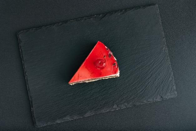 Vista superior em um pedaço de bolo de frutas vermelhas na bandeja de pedra preta.