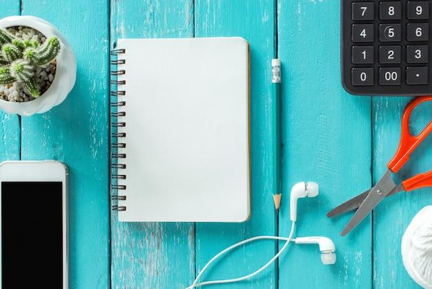 Vista superior em uma mesa de madeira com smartphone, caderno, lápis e flor, configuração plana.