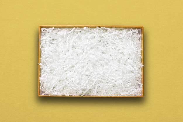 Vista superior, enchimento de papel branco em caixa de papelão amarela