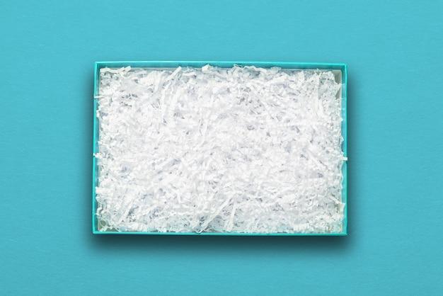 Vista superior, enchimento de papel branco em caixa de papelão azul