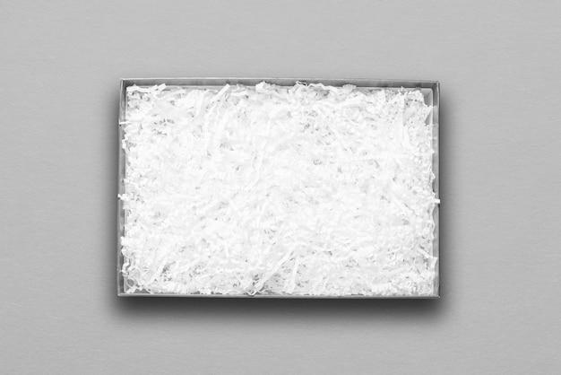 Vista superior, enchimento de papel branco em caixa de papelão cinza