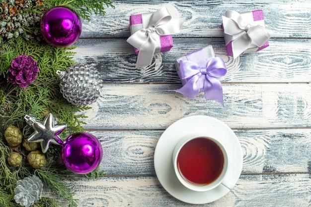 Vista superior enfeite de natal uma xícara de chá pequenos presentes galhos de árvore de abeto brinquedos de natal em superfície de madeira
