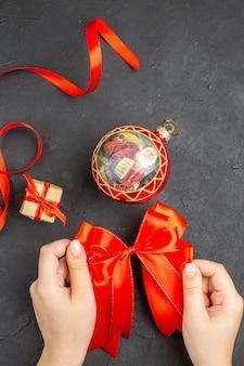 Vista superior enfeites de natal com arco vermelho em fundo bege