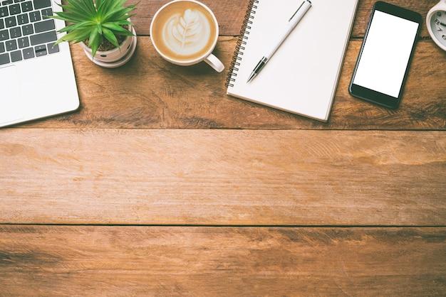 Vista superior equipamento de escritório, incluindo laptop, telefone celular, mouse, notebook, xícara de café no piso de madeira