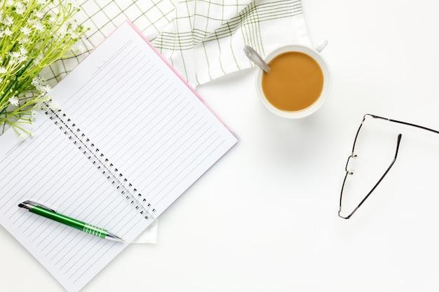 Vista superior, escritório de escritório, cartão, óculos, lindas flores brancas, café, caderno, guardanapo na mesa de escritório branca com espaço de cópia.