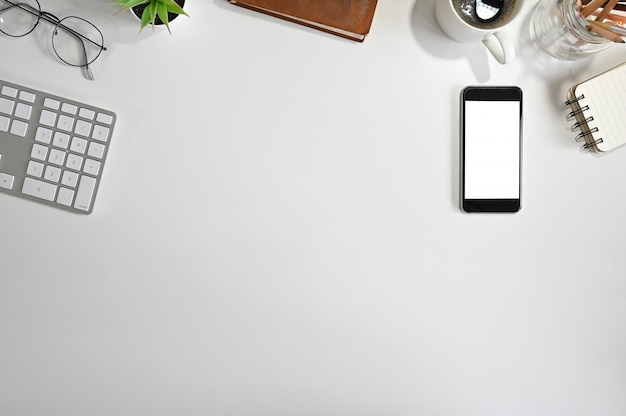 Vista superior escritório mesa maquete smartphone, teclado de computador, café, papel de bloco de notas na mesa branca.