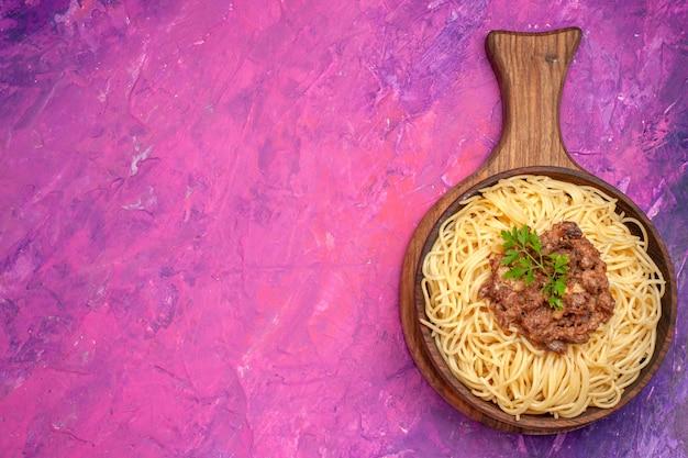 Vista superior espaguete cozido com carne moída em prato de massa de macarrão de mesa rosa