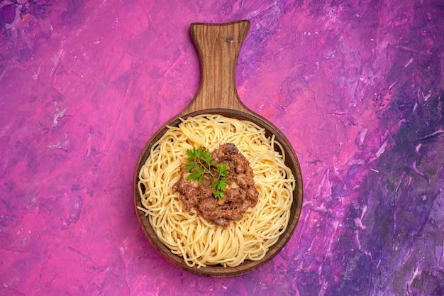 Vista superior espaguete cozido com carne moída em prato de massa de macarrão de piso rosa