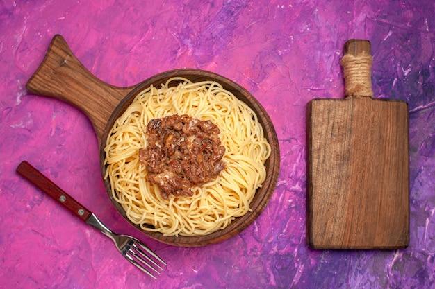 Vista superior espaguete cozido com carne moída em tempero de prato de massa de massa de mesa rosa