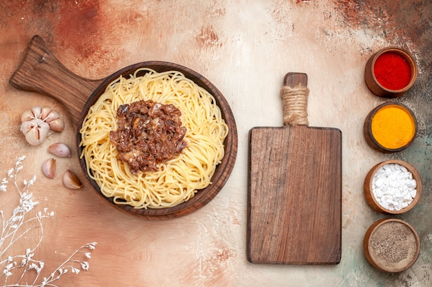 Vista superior espaguete cozido com carne moída em um prato de madeira, tempero para massa de macarrão