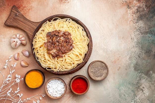 Vista superior espaguete cozido com carne moída em um prato de massa de massa de mesa de madeira tempero