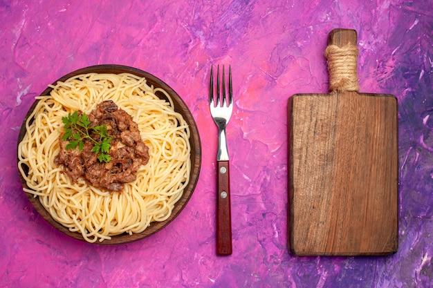 Vista superior espaguete cozido com carne moída na massa de massa de mesa rosa