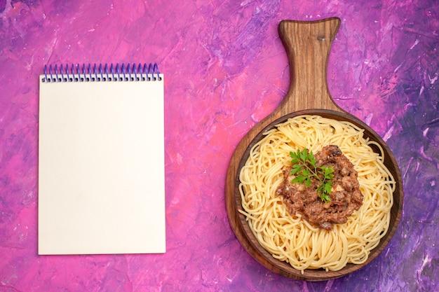 Vista superior espaguete cozido com carne moída na massa do prato de tempero de macarrão de mesa rosa