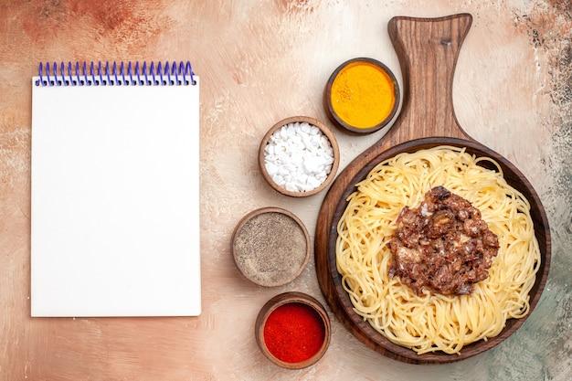 Vista superior espaguete cozido com carne moída sobre carne de prato de macarrão de mesa leve