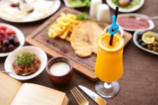 Vista superior espremido na hora suco de laranja com uma fatia de laranja em uma mesa de servir