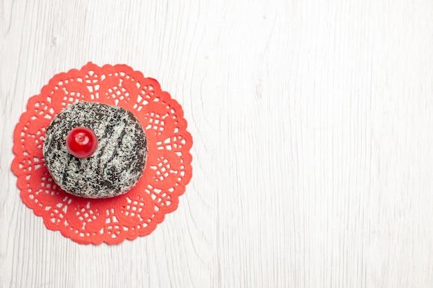 Vista superior esquerda do bolo de cacau com cereja azeda no guardanapo de renda oval vermelha na mesa de madeira branca