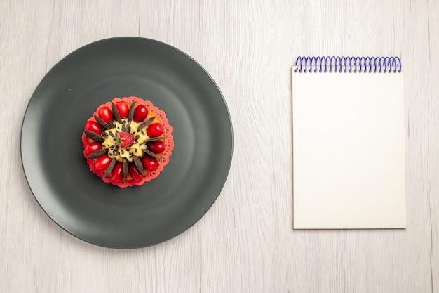Vista superior esquerda do bolo de chocolate arredondado com cornel e framboesa no centro na placa cinza e um caderno no fundo branco de madeira