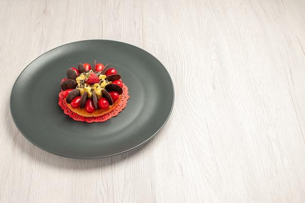 Vista superior esquerda do bolo de chocolate arredondado com cornel e framboesa no centro na placa cinza sobre a mesa de madeira branca