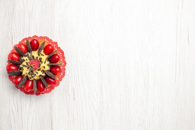 Vista superior esquerda do bolo de chocolate com frutas vermelhas no guardanapo de renda oval vermelha sobre a mesa de madeira branca
