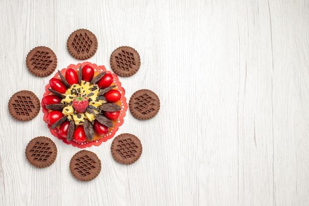 Vista superior esquerda do bolo de frutas vermelhas no guardanapo de renda oval vermelha e biscoitos na mesa de madeira branca