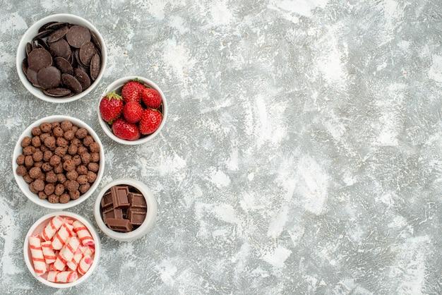 Vista superior esquerda tigelas com doces, morangos, chocolates amargos e leitosos, cereais e cacau no fundo branco-acinzentado