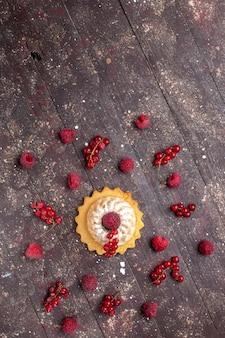 Vista superior extremamente distante, delicioso pequeno bolo com açúcar em pó junto com framboesas e cranberries ao longo da mesa marrom, biscoito de bolo de frutas vermelhas