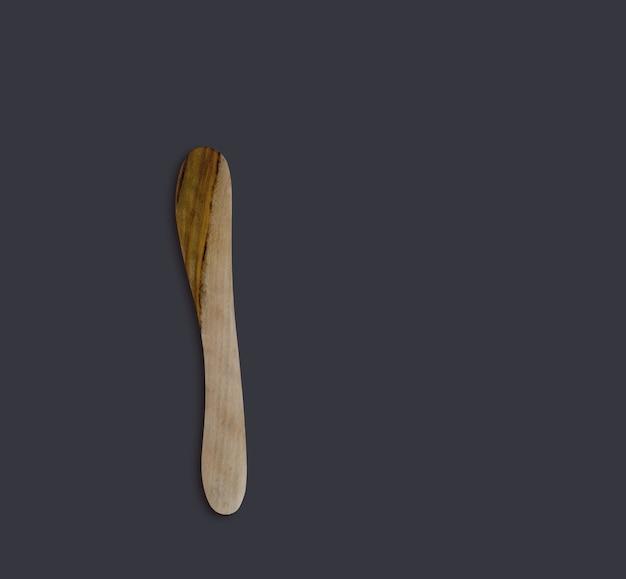 Vista superior faca de manteiga de madeira verde-oliva isolada no preto