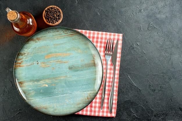 Vista superior faca e garfo de prato redondo pimenta preta em garrafa de óleo pequena e guardanapo xadrez vermelho e branco na mesa preta