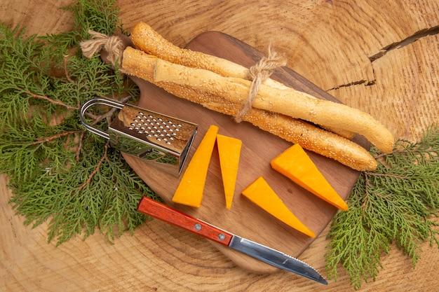 Vista superior faca ralador de caixa de pão e queijo na tábua de cortar galhos de árvores de pinho na mesa de madeira